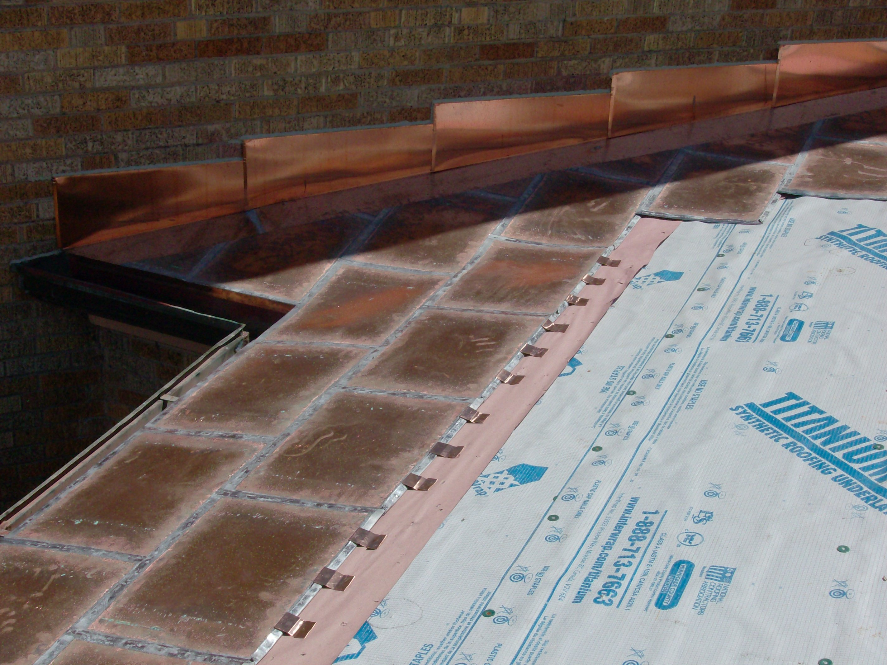 Copper flat lock roof and stepped copper counter flashing.