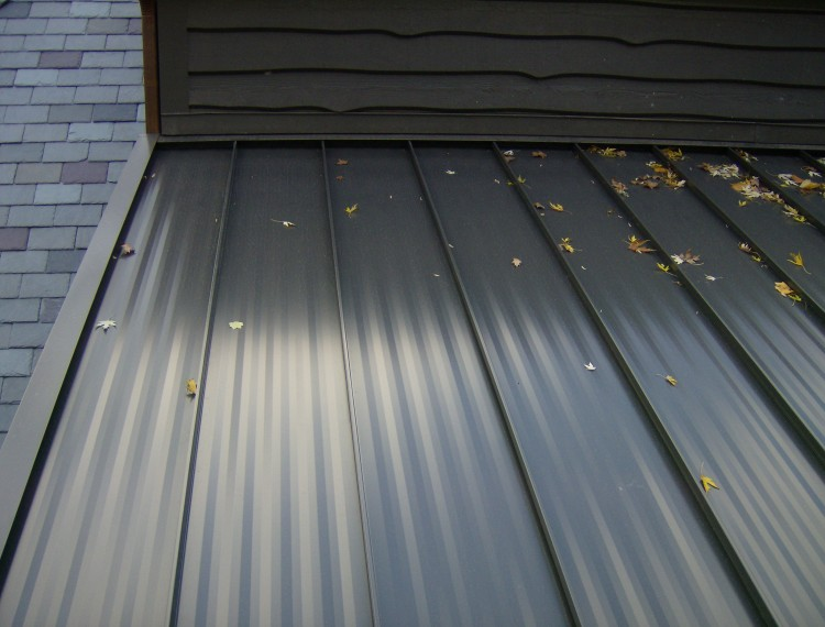 Standing seam painted steel roof - view of panel striations and headwall flashing.