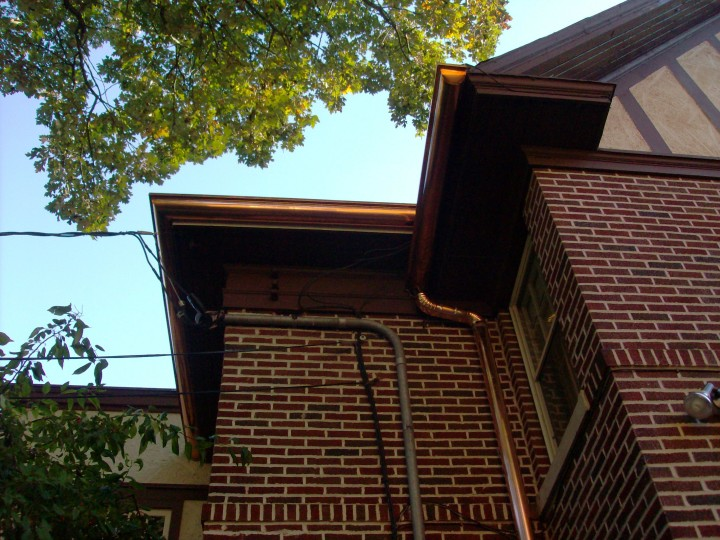 Custom copper half-round gutters and downspout under modified bitumen flat roof.